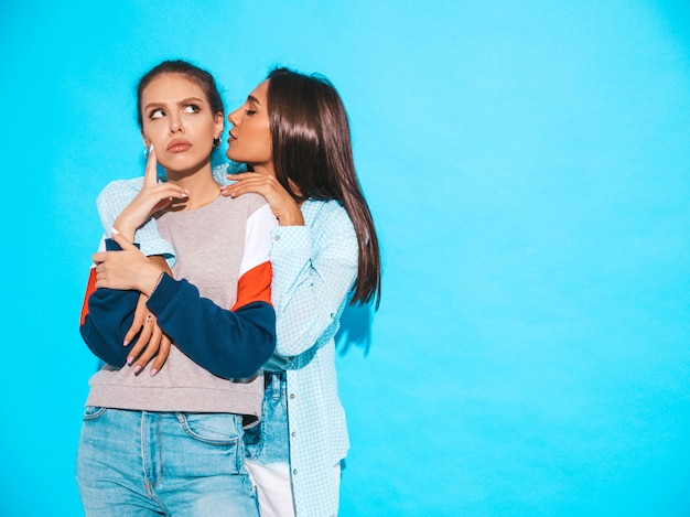 トレンディな夏のカジュアルな服で2人の若い美しい笑顔流行に敏感な女の子。セクシーな女性が秘密を共有し、ゴシップ。青に分離。驚いた顔の感情