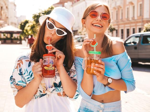 Две молодые красивые улыбающиеся битник девушки в модной летней одежде и панама шляпу.