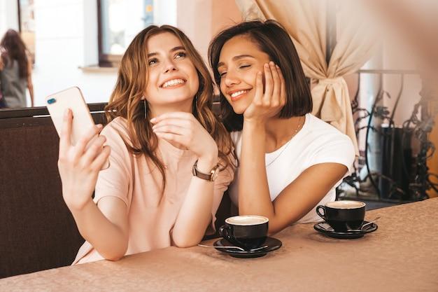 トレンディな夏服の2人の若い美しい笑顔の流行に敏感な女の子。ベランダテラスカフェでチャットやコーヒーを飲んで屈託のない女性。