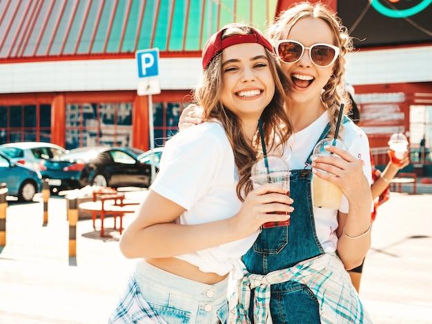 Две молодые красивые улыбающиеся хипстерские девушки в модной летней одежде выпивают