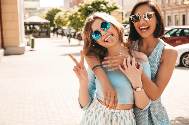 トレンディな夏服で2人の若い美しい笑顔の流行に敏感な女の子。サングラスで通りの背景にポーズセクシーな屈託のない女性。楽しくてハグしているポジティブモデルピースサインを見せて