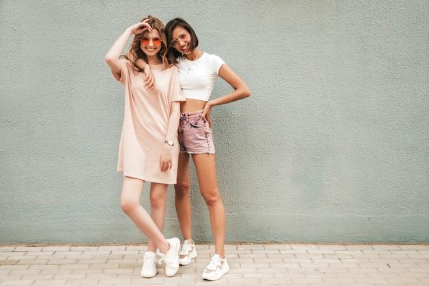 Две молодые красивые улыбающиеся хипстерские девочки в модной летней одежде. сексуальные беззаботные женщины, позирующие на уличном фоне в солнцезащитных очках. позитивные модели развлекаются и обнимаются