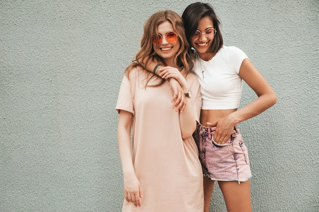 トレンディな夏服で2人の若い美しい笑顔の流行に敏感な女の子。サングラスで通りの背景にポーズセクシーな屈託のない女性。楽しくてハグするポジティブモデル