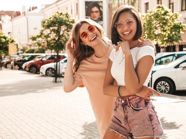 トレンディな夏服の2人の若い美しい笑顔流行に敏感な女の子。サングラスで通りの背景にポーズセクシーな屈託のない女性。楽しくてクレイジーになるポジティブモデル