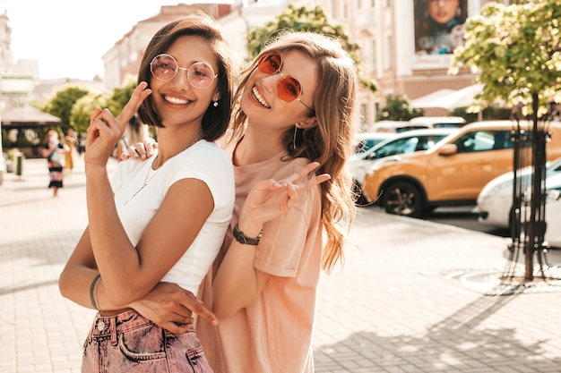 トレンディな夏服の2人の若い美しい笑顔流行に敏感な女の子。サングラスで通りの背景にポーズセクシーな屈託のない女性。楽しくてハグしているポジティブモデル。