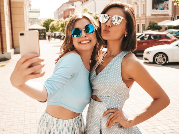 Две молодые красивые улыбающиеся битник девушки в модной летней одежде. сексуальные беззаботные женщины, позирует на фоне улицы в солнцезащитные очки. они делают селфи автопортрет на смартфоне на закате
