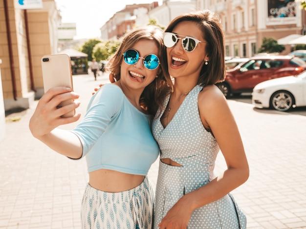 トレンディな夏服の2人の若い美しい笑顔流行に敏感な女の子。サングラスで通りの背景にポーズセクシーな屈託のない女性。夕暮れ時にスマートフォンで自分撮り写真を撮る
