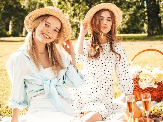 Две молодые красивые улыбающиеся хипстерские девушки в модном летнем сарафане и шляпах. беззаботные женщины делают пикник на улице.