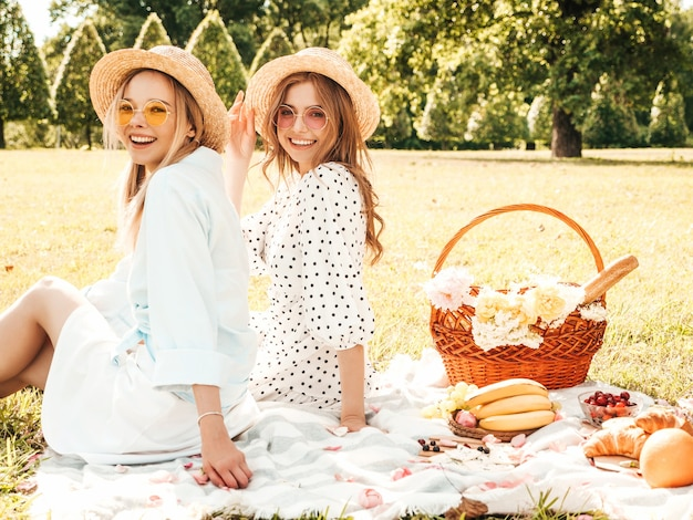 트렌디한 여름 sundress와 모자에 두 젊은 아름 다운 웃는 hipster 소녀. 바깥에서 피크닉을 만드는 평온한 여성.