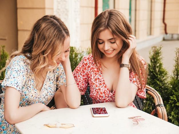 トレンディな夏のサンドレスの2人の美しい笑顔の流行に敏感な若い女の子。