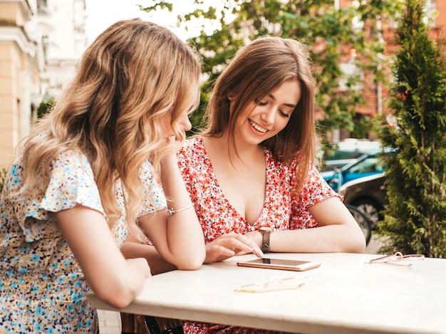 Две молодые красивые улыбающиеся хипстерские девушки в модном летнем сарафане. беззаботные женщины, болтающие в кафе на веранде. модель показывает информацию о своем друге в своем смартфоне. они смотрят фотографии после покупок