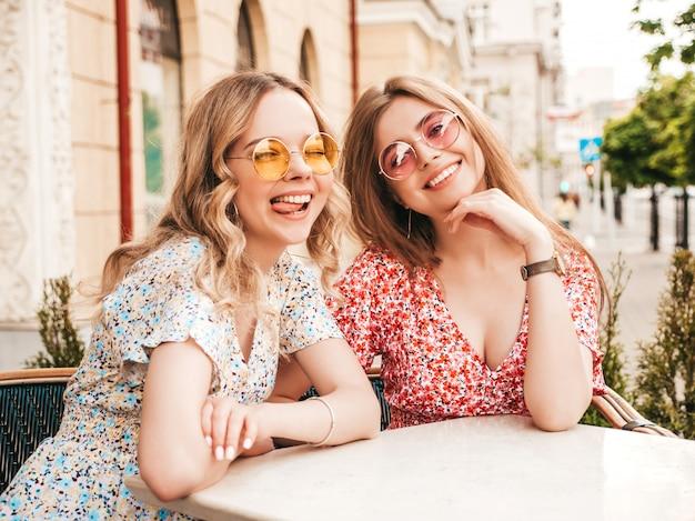 Две молодые красивые улыбающиеся хипстерские девушки в модном летнем сарафане. беззаботные женщины в чате на веранде кафе на фоне улиц в солнцезащитных очках. позитивные модели с удовольствием и общение