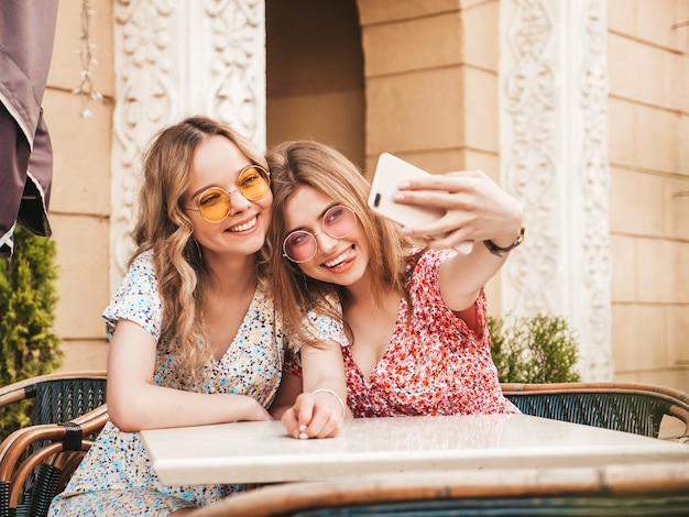 Две молодые красивые улыбающиеся битник девушки в модном летнем сарафане. беззаботные женщины в чате на веранде кафе на фоне улицы. позитивные модели с удовольствием и и принимая селфи на смартфоне