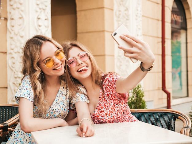 トレンディな夏のサンドレスで2人の若い美しい笑顔の流行に敏感な女の子。通りの背景にあるベランダカフェでチャットの屈託のない女性。