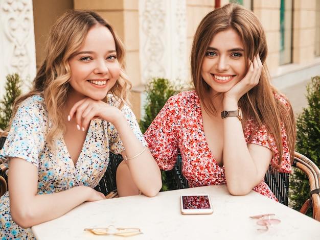 トレンディな夏のサンドレスで2人の若い美しい笑顔の流行に敏感な女の子。通りの背景のベランダカフェでチャットののんきな女性。