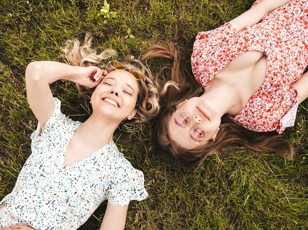 유행 여름 sundress에 두 젊은 아름 다운 웃는 hipster 여자. 선글라스에 푸른 잔디에 누워 섹시 평온한 여자. 재미있는 모델 재미.