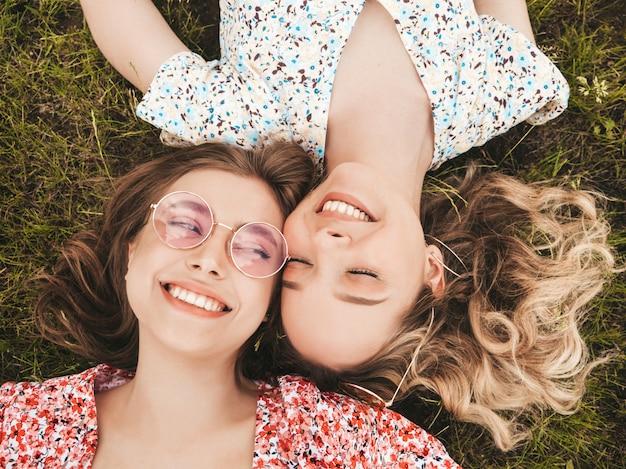 Две молодые красивые улыбающиеся хипстерские девушки в модном летнем сарафане. сексуальные беззаботные женщины, лежащие на зеленой траве в солнцезащитных очках. позитивные модели с удовольствием. вид сверху