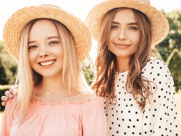 トレンディな夏のサンドレスで2人の若い美しい笑顔のヒップスターの女の子。帽子をかぶって公園でポーズをとるセクシーな屈託のない女性。
