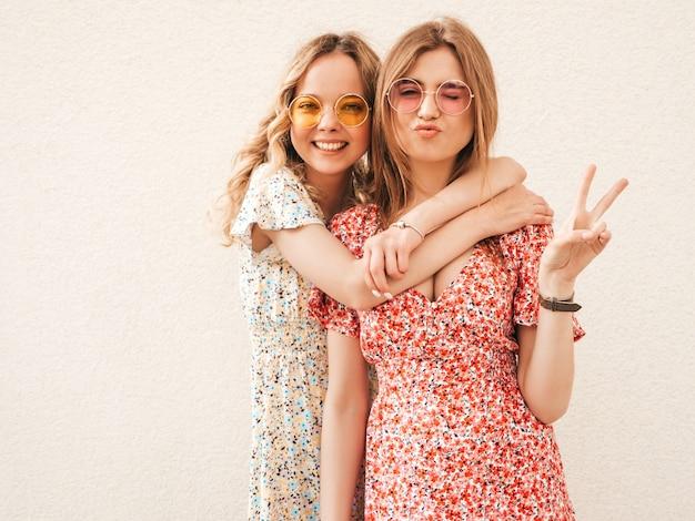Две молодые красивые улыбающиеся битник девушки в модном летнем сарафане. сексуальные беззаботные женщины позируют на улице возле стены в солнцезащитные очки. позитивные модели развлекаются и показывают знак мира