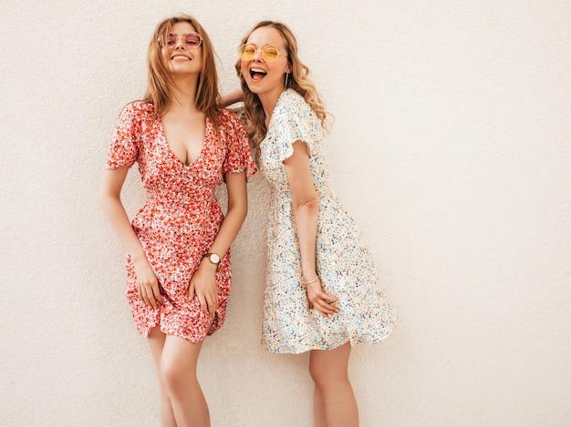 Две молодые красивые улыбающиеся битник девушки в модном летнем сарафане. сексуальные беззаботные женщины, позирует возле стены на фоне улицы в солнцезащитные очки. позитивные модели развлекаются и обнимаются