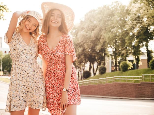 유행 여름 sundress에 두 젊은 아름 다운 웃는 hipster 여자. 일몰에 모자에 거리 배경에 포즈 섹시 평온한 여자. 재미와 포옹을 가진 긍정적 인 모델