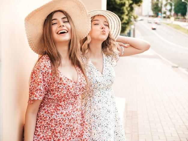 Две молодые красивые улыбающиеся битник девушки в модном летнем сарафане. сексуальные беззаботные женщины, позирует на фоне улицы в шляпах. позитивные модели развлекаются и обнимаются. они сходят с ума