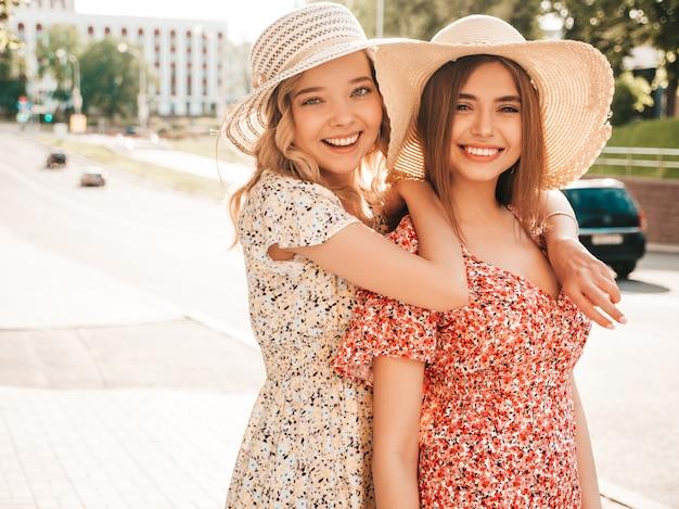 유행 여름 sundress에 두 젊은 아름 다운 웃는 hipster 여자. 모자에 거리 배경에 포즈 섹시 평온한 여자. 재미 있고 포옹하는 긍정적 인 모델.