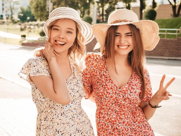 Две молодые красивые улыбающиеся битник девушки в модном летнем сарафане. сексуальные беззаботные женщины, позирует на фоне улицы в шляпах. позитивные модели развлекаются и обнимаются. они показывают знак мира и язык