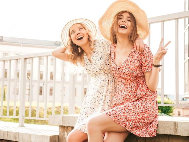 유행 여름 sundress에 두 젊은 아름 다운 웃는 hipster 여자. 모자에 거리 배경에 포즈 섹시 평온한 여자. 재미와 포옹을 가진 긍정적 인 모델.