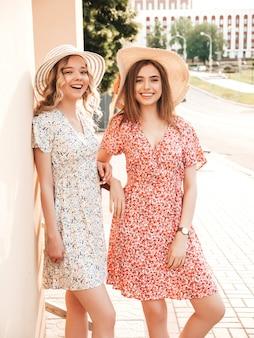 トレンディな夏のサンドレスで2人の若い美しい笑顔の流行に敏感な女の子。帽子で通りの背景にポーズセクシーな屈託のない女性。楽しくてハグするポジティブモデル