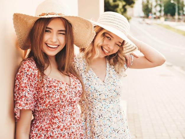 유행 여름 sundress에 두 젊은 아름 다운 웃는 hipster 여자. 모자에 거리 배경에 포즈 섹시 평온한 여자. 재미와 포옹을 가진 긍정적 인 모델