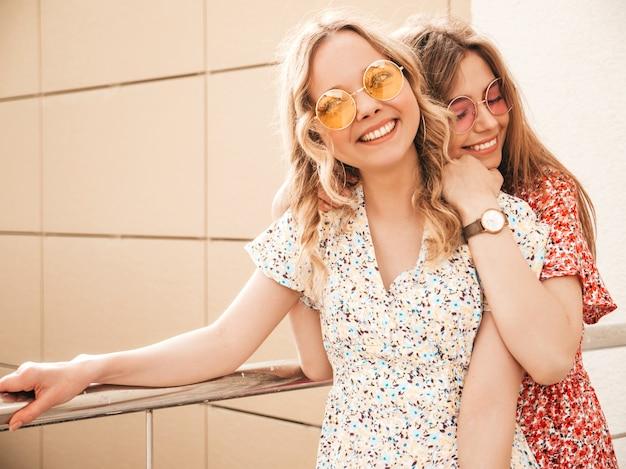 トレンディな夏のサンドレスで2人の若い美しい笑顔の流行に敏感な女の子。セクシーな屈託のない女性がサングラスで通りの背景にポーズします。楽しくてクレイジーになるポジティブモデル