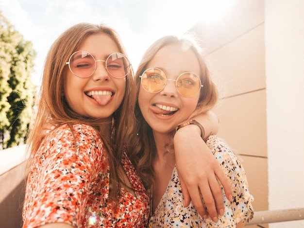 トレンディな夏のサンドレスで2人の若い美しい笑顔の流行に敏感な女の子。セクシーな屈託のない女性がサングラスで通りの背景にポーズします。夕暮れ時にスマートフォンで自分撮り写真を撮る