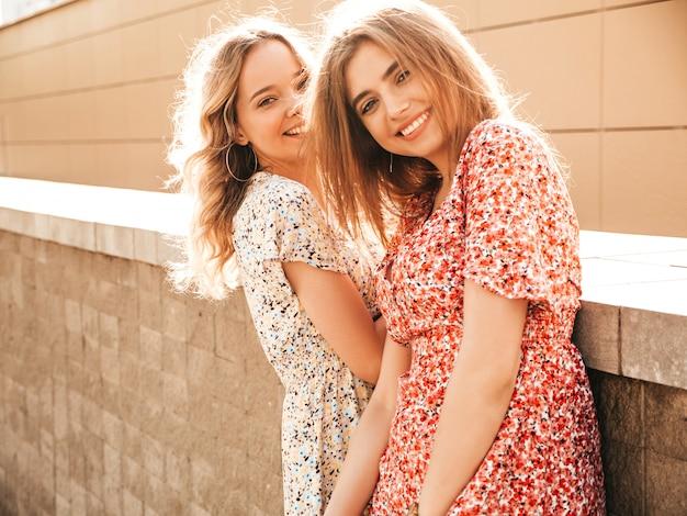 유행 여름 sundress에 두 젊은 아름 다운 웃는 hipster 여자. 거리 배경에 포즈 섹시 평온한 여자. 재미 있고 미쳐가는 긍정적 인 모델