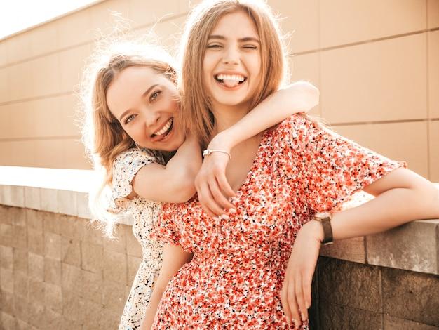 유행 여름 sundress에 두 젊은 아름 다운 웃는 hipster 여자. 거리 배경에 포즈 섹시 평온한 여자. 재미 있고 혀를 보여주는 긍정적 인 모델