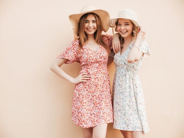 トレンディな夏のサンドレスで2人の若い美しい笑顔流行に敏感な女の子。帽子の壁の近くの通りでポーズセクシーな屈託のない女性。楽しくてハグするポジティブモデル