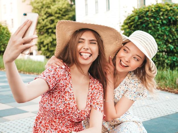 トレンディな夏のサンドレスで2人の若い美しい笑顔の流行に敏感な女の子。帽子で通りの背景に座っているセクシーな屈託のない女性。スマートフォンで自撮り写真を撮るポジティブモデル