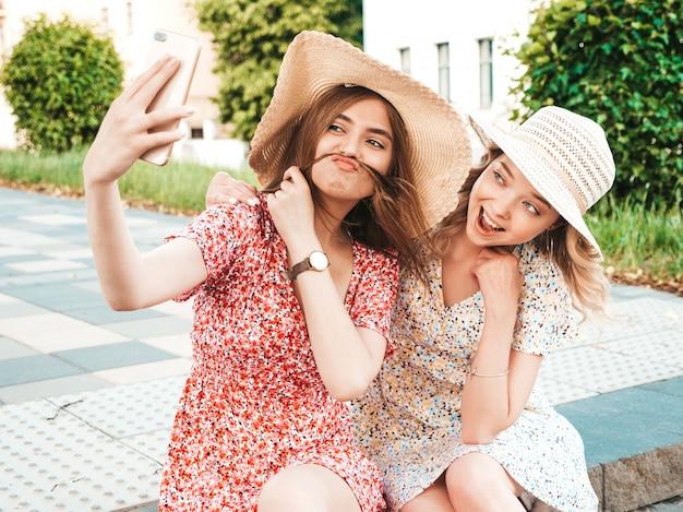 유행 여름 sundress에 두 젊은 아름 다운 웃는 hipster 여자. 모자에 거리 배경에 앉아 섹시 평온한 여자. 스마트 폰에서 셀카 자화상 사진을 찍는 긍정적 인 모델