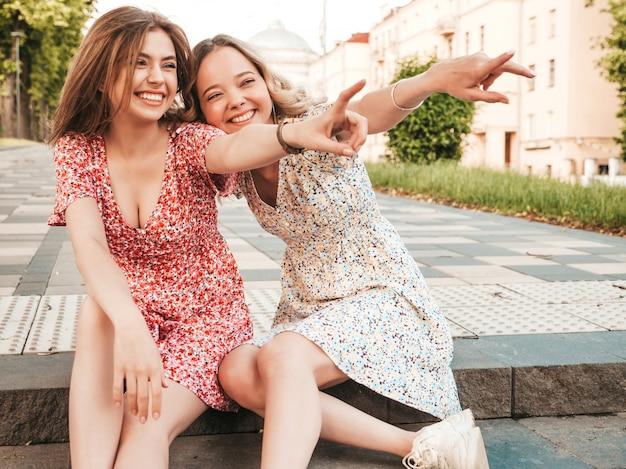 Две молодые красивые улыбающиеся битник девочки в модный летний сарафан. сексуальные беззаботные женщины, сидя на фоне улицы. позитивные модели веселятся и обнимаются. они указывают на что-то интересное