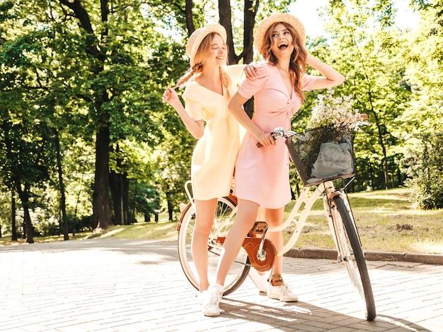 トレンディな夏のサンドレスで2人の若い美しい笑顔のヒップスターの女の子