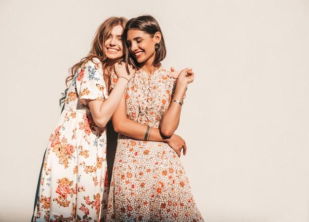 Две молодые красивые улыбающиеся хипстерские девушки в модных летних сарафанах