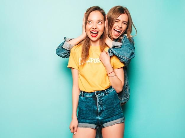 Две молодые красивые улыбающиеся хипстерские девушки в модных летних желтых футболках и джинсовой куртке. сексуальные беззаботные женщины позируют возле синей стены. модные и позитивные модели с удовольствием