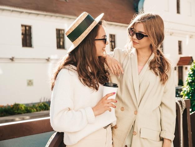 트렌디한 흰색 스웨터와 코트를 입은 두 젊은 아름다운 미소 힙스터 소녀