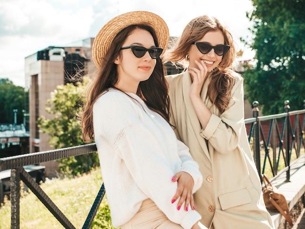 トレンディな白いセーターとコートで2人の若い美しい笑顔のヒップスターの女の子