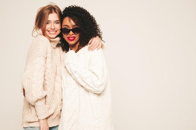 トレンディな冬のセーターを着た2人の若い美しい笑顔のヒップスターの女の子。楽しさと抱擁を持っているポジティブモデル