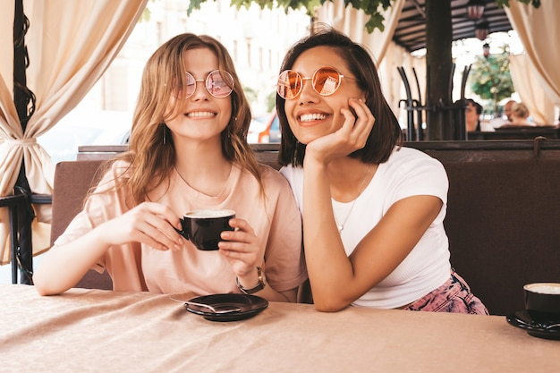 Two young beautiful smiling hipster girls in trendy summer casual clothes.carefree women chatting in veranda terrace cafe and drinking coffee.positive models having fun and communicating