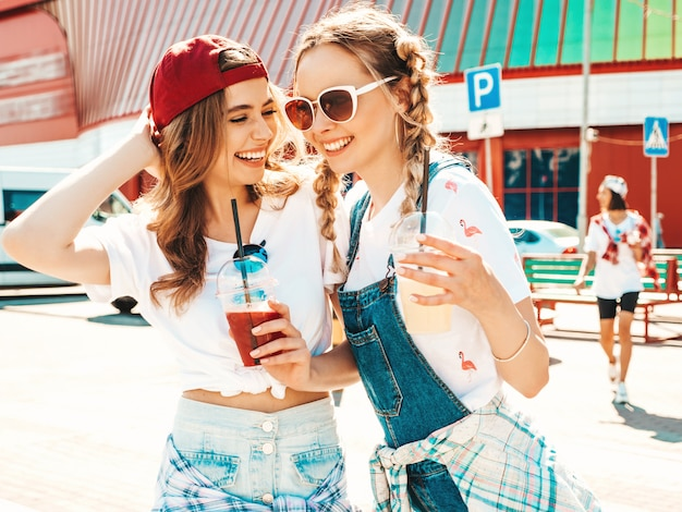 Two young beautiful smiling hipster girls in trendy summer clothes having a drink