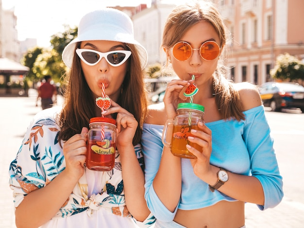 Two young beautiful smiling hipster girls in trendy summer clothes and panama hat.