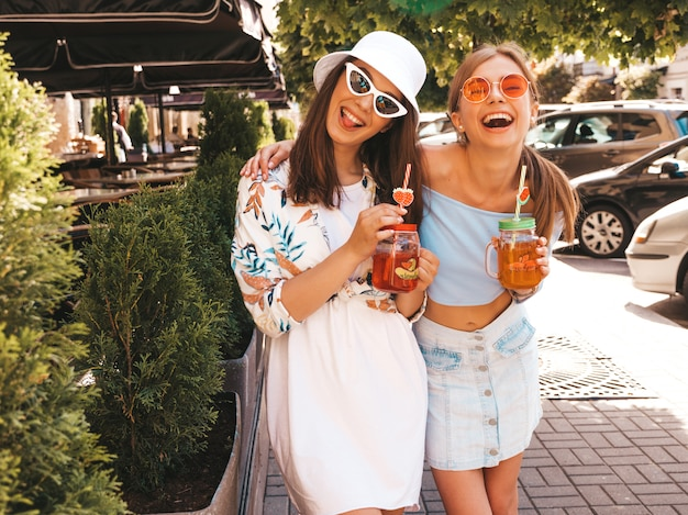 Two young beautiful smiling hipster girls in trendy summer clothes and panama hat