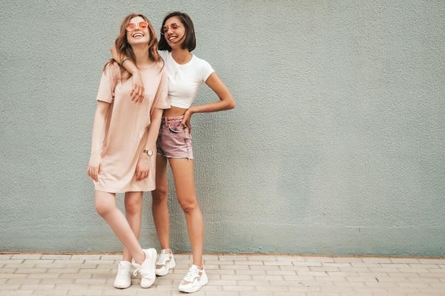 Due giovani belle ragazze sorridenti dei pantaloni a vita bassa in vestiti alla moda di estate. donne spensierate sexy che posano vicino alla parete nella via in occhiali da sole. modelli positivi che si divertono e si abbracciano